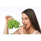 Young woman eating fresh grapes